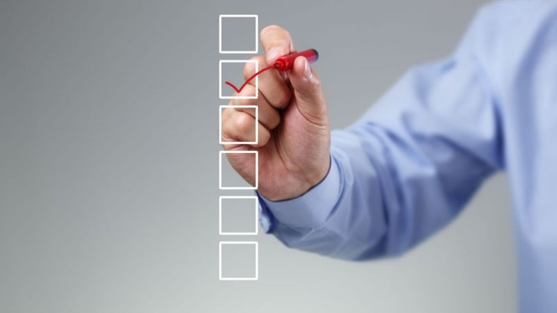 Stift in der Hand kreuzt Box in einer Checkliste an