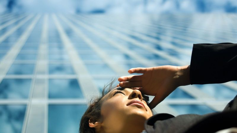 Von unten fotografiert: Das Gesicht einer Frau, die ihre Hand an die Stirn hält, um in die Ferne zu schauen. Im Hintergrund die Glausfront eines Hochhauses in dem sich der blaue Himmel spiegelt..