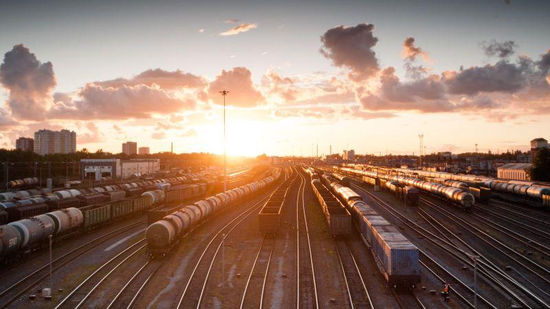 Blick über mehrere Güterzüge auf Abstellgleisen bei Sonnenuntergang