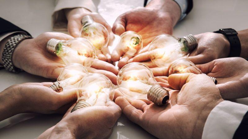 Symbolbildfür gemeinsame Ideen: Kreis aus mehreren Händen. Auf jeder Handfläche liegt eine leuchtende Glühbirne.