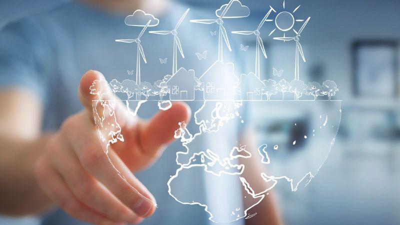 Symbolbild Hand berührt Hologramm : die untere Hälfte zeigt eine halbe Weltkugel, die obere Hälfte Windräder, Häuser, Bäume, die Sonne und Schmetterlinge
