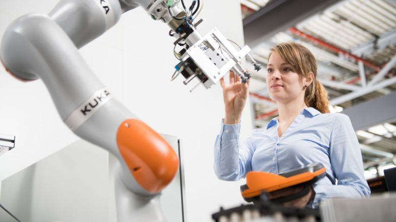 Eine junge Frau programmiert einen Roboter, der in der Produktion kleinere Losgrößen ermöglicht.