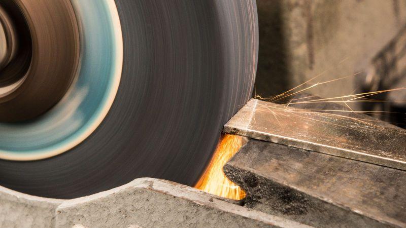 An einer Schleifmaschine wird ein Metallstück bearbeitet.