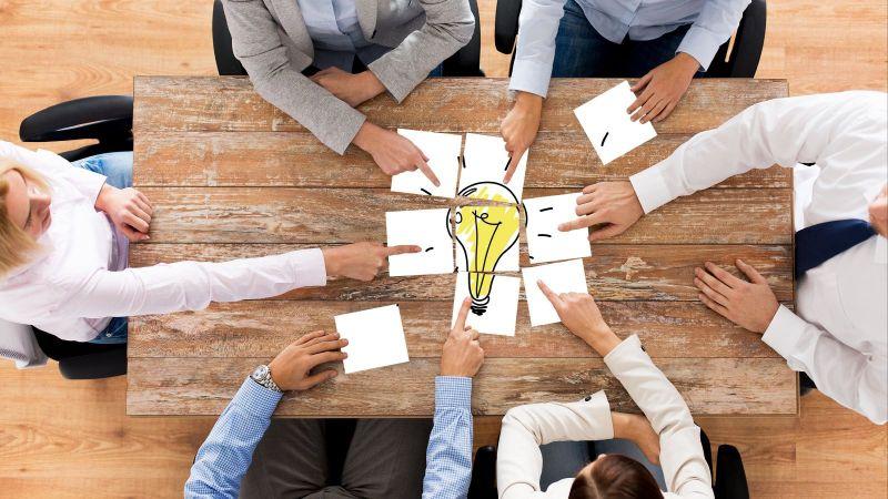Symbolbild: Mehrere Personen sitzen an einem Tisch und legen Papierstücke in die Mitte. Zusammen ergeben diese das Bild einer Glühbirne.