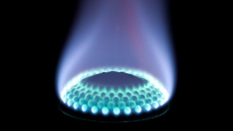 Eine blau Gasflamme ist auf dunklem Hintergrund zu sehen.