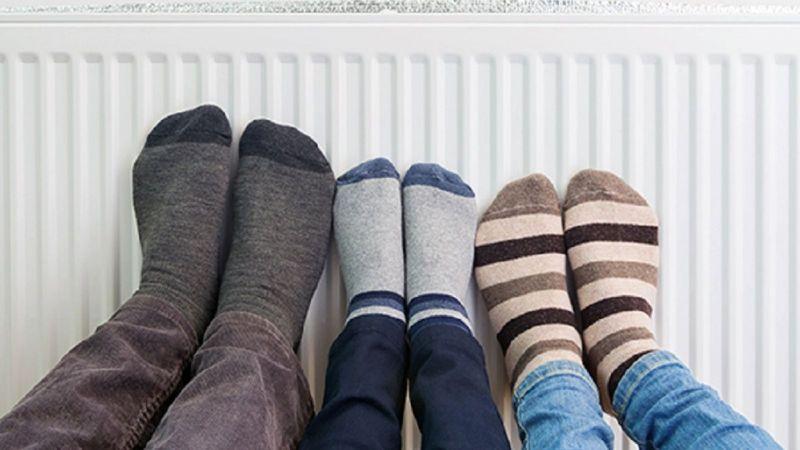 Symbolbild: Zwei Erwachsene und ein Kind wärmen ihre Füße in Socken an einem Heizkörper.