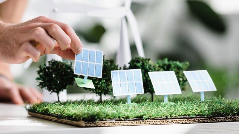Es ist eine Hand zu sehen, die ein Modell eines Solarmoduls auf eine modellierte Grünfläche stellt.