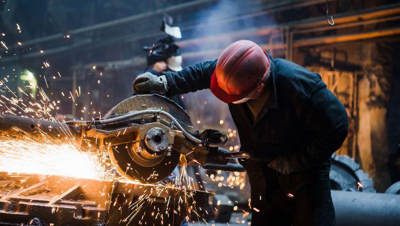Ein Arbeiter schneidet heißes Metall mit einer Sägemaschine - es sprühen Funken.