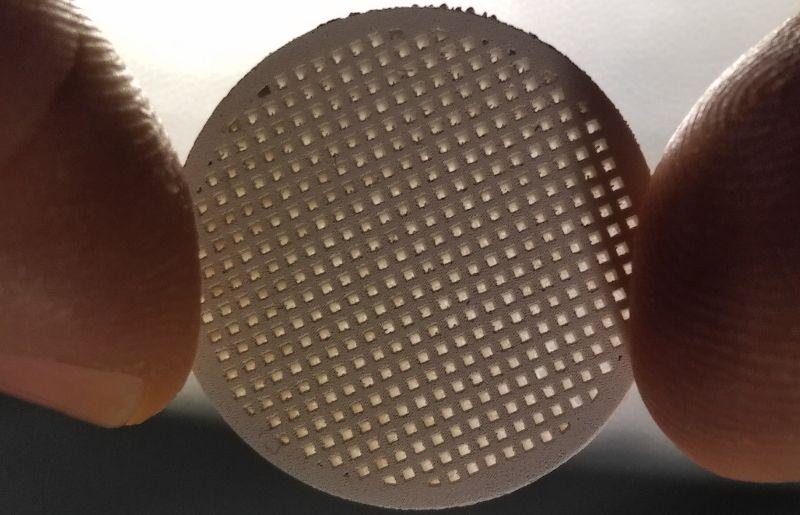 Lichtschein durch die Poren eines runden Membranträgers aus Magnesiumoxid, der im 3D-Siebdruck hergestellt wurde