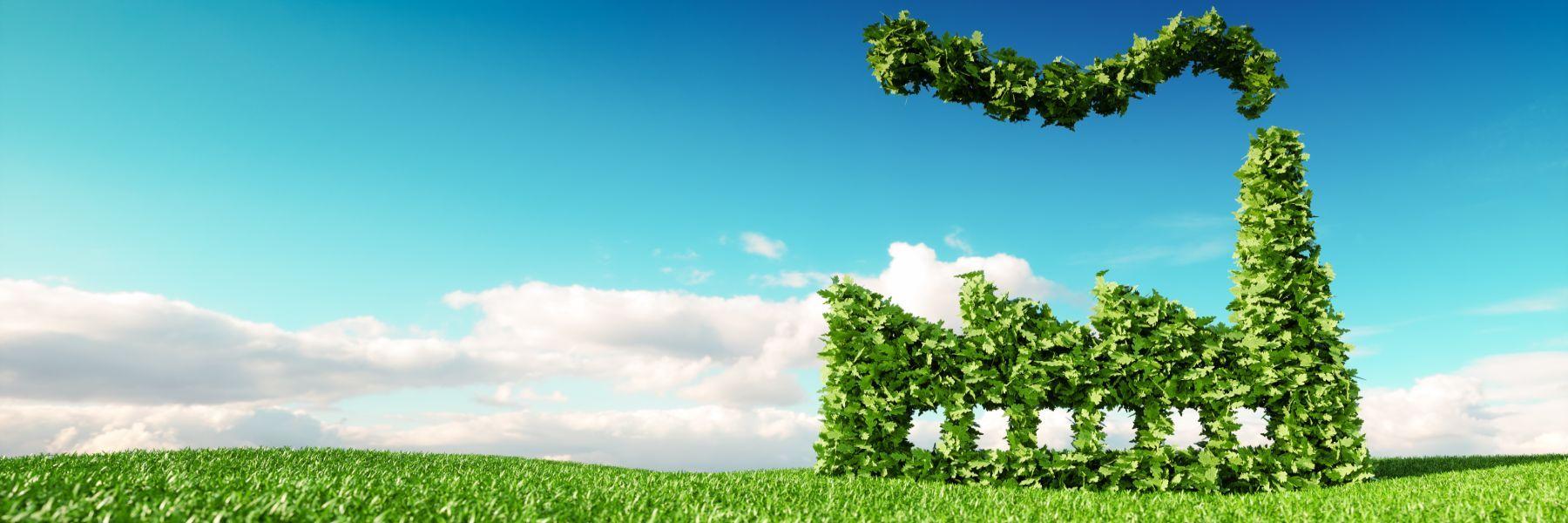 Symbolisch aus grünen Blättern grafisch dargestellte Fabrik auf Wiese mit blauem Himmel