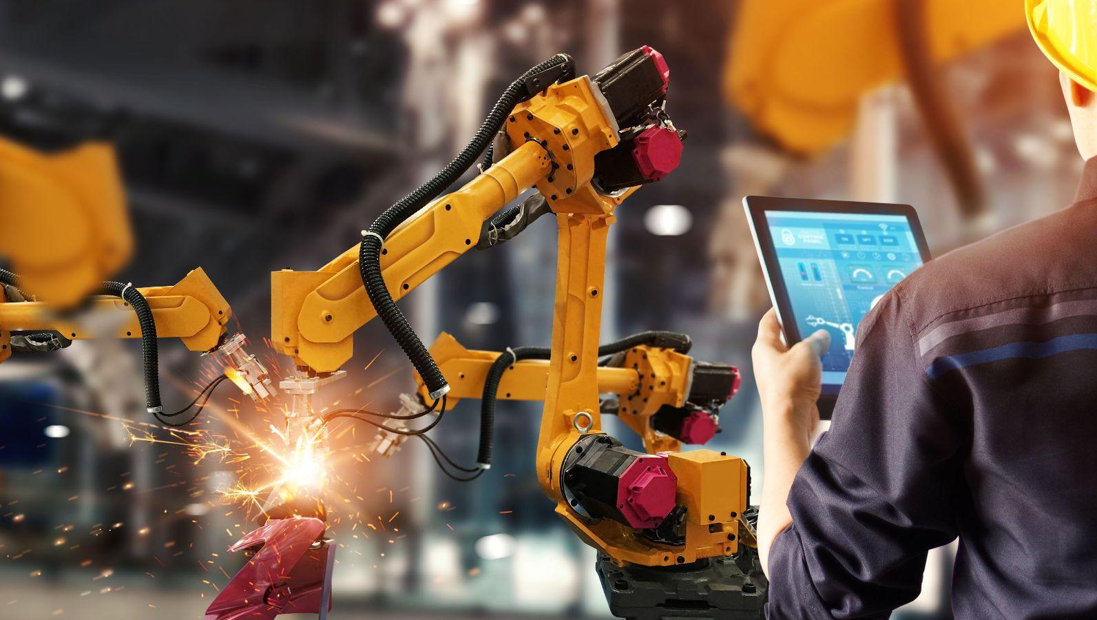 Arbeiter von hinten mit Tablet, der damit die Arbeit zweier Roboterarme überprüft