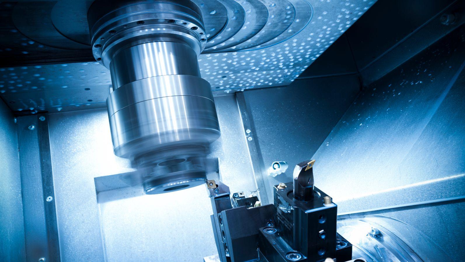 Innenansicht einer CNC-Drehmaschine. Der Maschinenkopf dreht sich für die spanende Bearbeitung eines Bauteils.