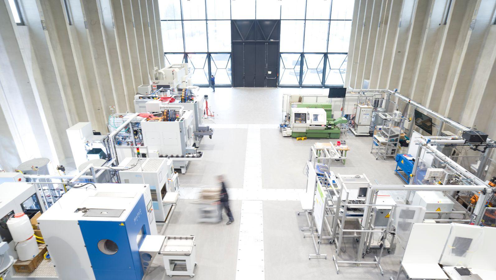 Die Halle der Forschungsfabrik ETA-Fabrik von oben mit mehreren Maschinen einer metallverarbeitenden Produktion.