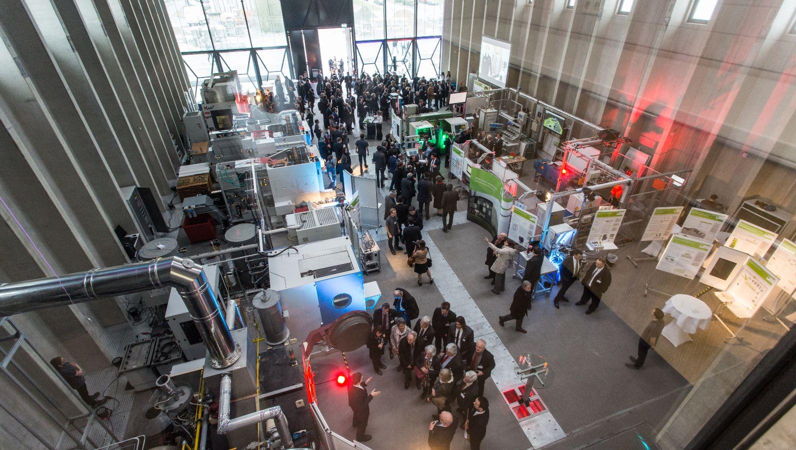 Halle der ETA-Fabrik bei der Einwihungsfeier. BesucherInnen bestaunen die Maschinen in der Forschungsfabrik.