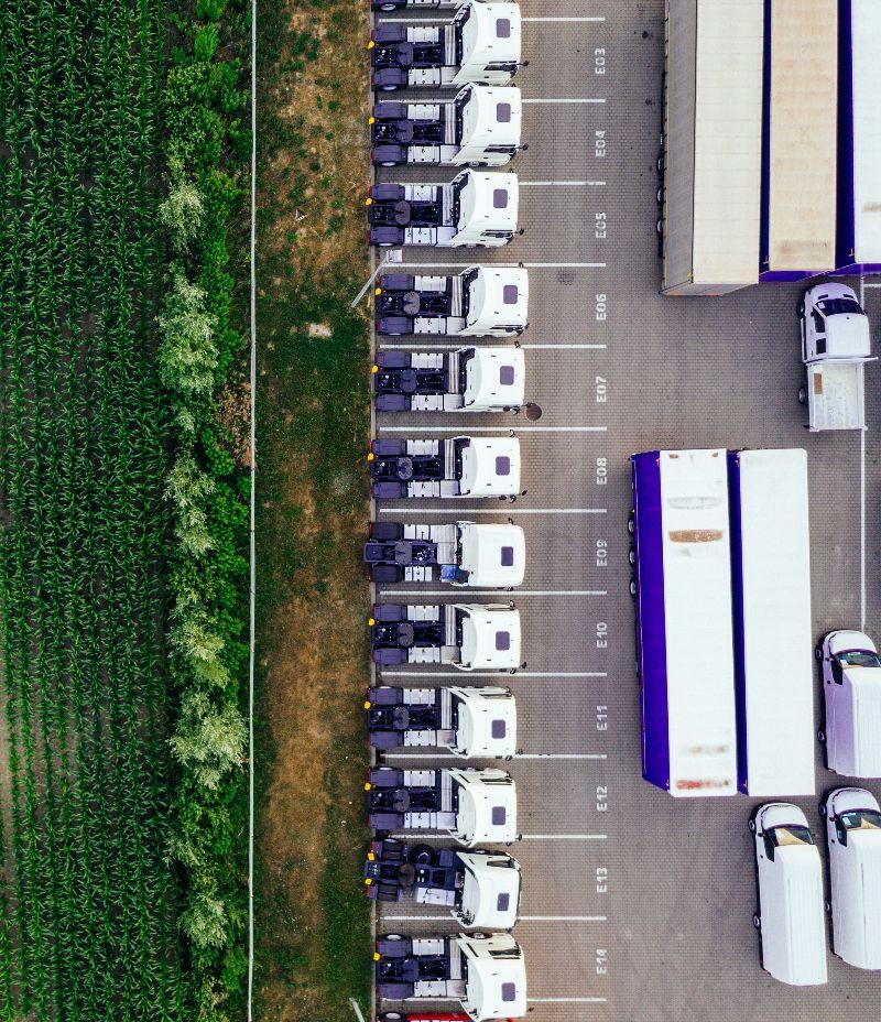Blick von oben auf den Parkplatz eines Unternehmens oder Logistikzenrums. Mehrere LKW-Führerstände sowie Anhänger sind nebeneinander geparkt.