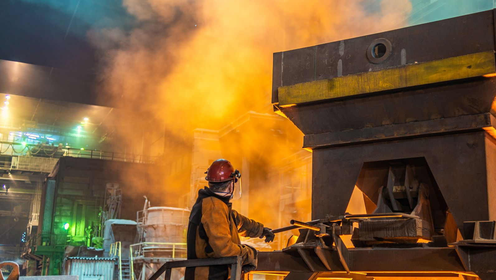 Energieintensive Industrie: Ein Arbeiter am Ofen im Stahlwerk mit glühender Hitze.