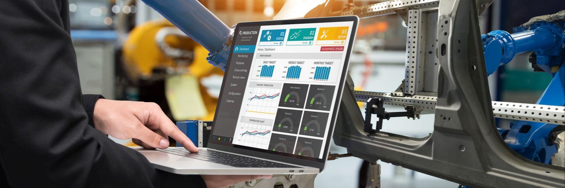 Digitalisierung in der Industrie: Laptop zeigt Diagramme und überwacht Produktionsanlagen, die im Hintergrund zu sehen sind.