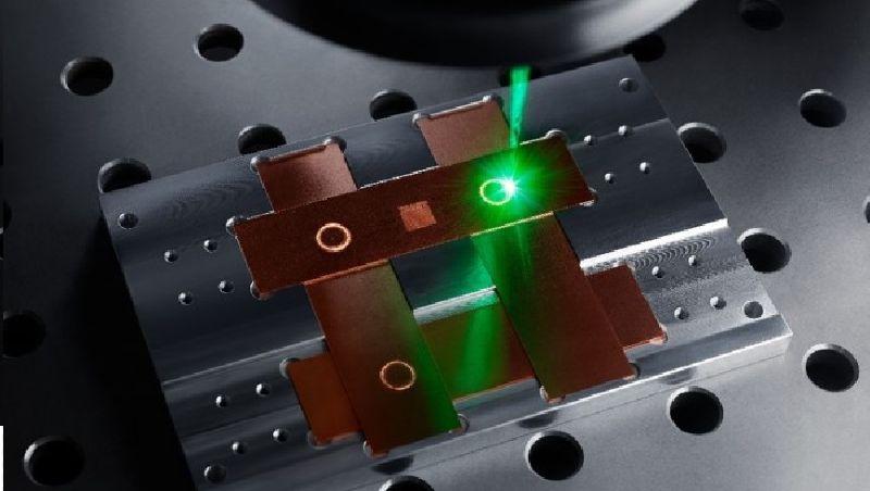 Ein grüner Laserstrahl trifft auf die Bauteile einer Leistungselektronik.