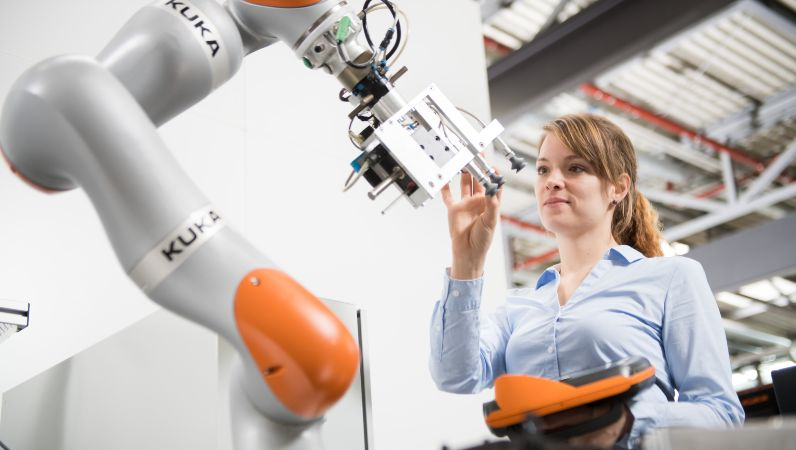 Eine junge Frau pogrammiert einen Roboter in der Produktion.