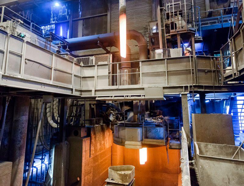 Produktionshalle zur Sekundärstahlerzeugung: glühende Graphitelektroden eines Elektrolichbogenofens
