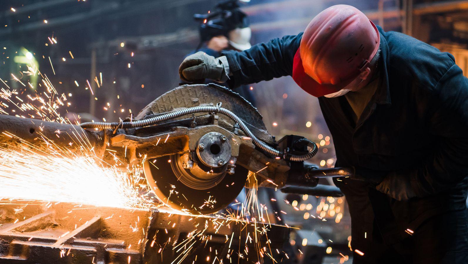 Arbeiter verarbeitet Stahl mit einer Sägemaschine. Das Metall ist heiß und es sprühen Funken.