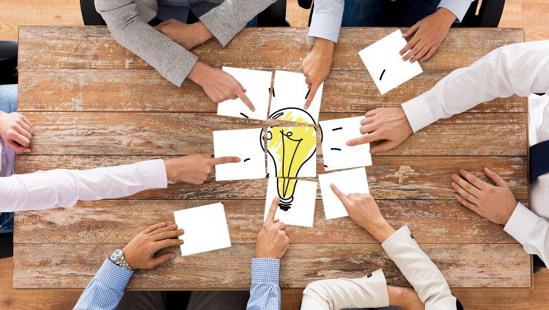 Mehrere Personen legen Papierstücke in der Mitte eines Tiesches zusammen. Das Bild, das dabei entsteht zeigt eine Glühbirne.