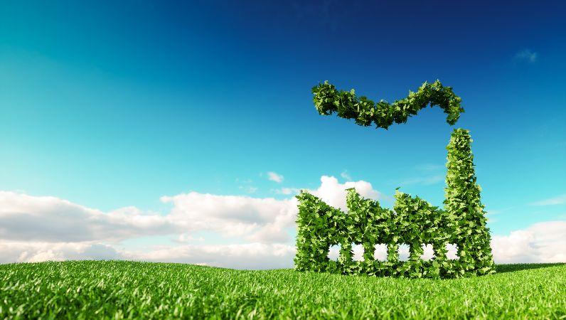 Darstellung eines grünen Fabriksymbols auf frischer Frühlingswiese mit blauem Himmel im Hintergrund
