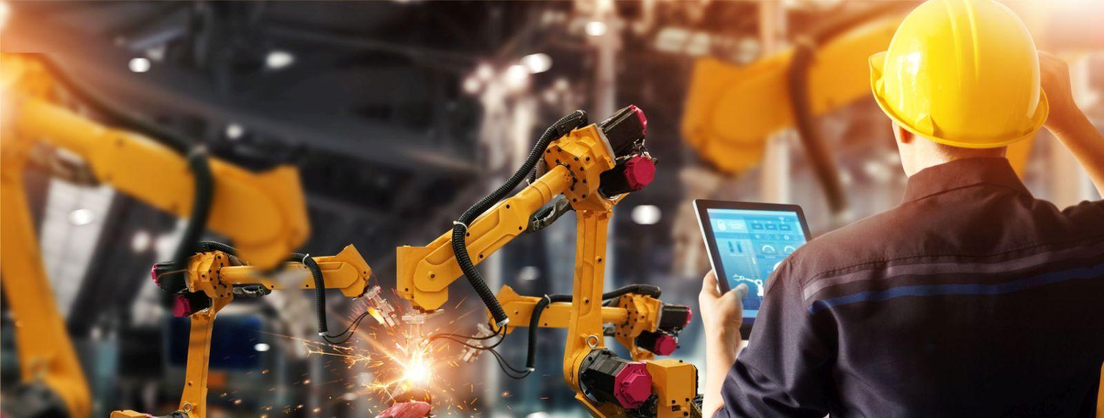 Symbolbild Künstliche Intelligenz: Arbeiter von hinten mit Laptop  vor 2 Roboterarmen in Industriehalle