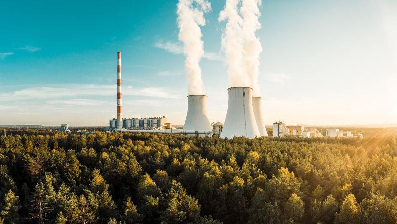 Industrieanlage im Wald mit drei Kraftwerkstürmen und Rauchwolken