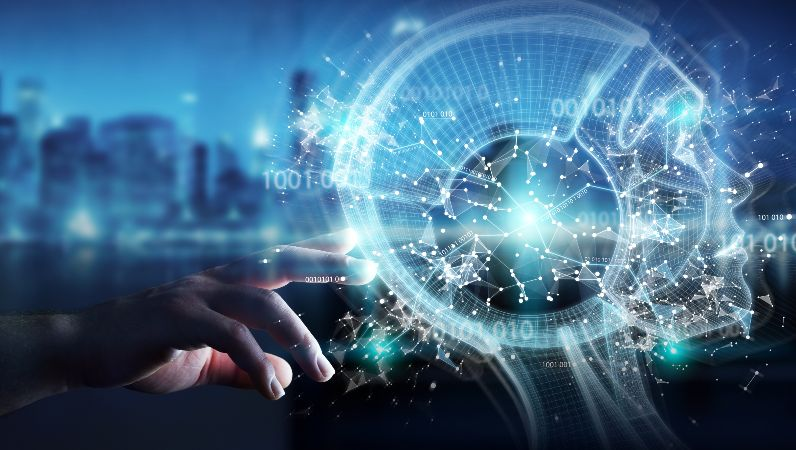 Eine menschliche Hand, welche ein virtuellen Kopf berührt, dieser stellt die künstliche Intelligenz dar. Im Hintergrund sind die Konturen einer Stadt.
