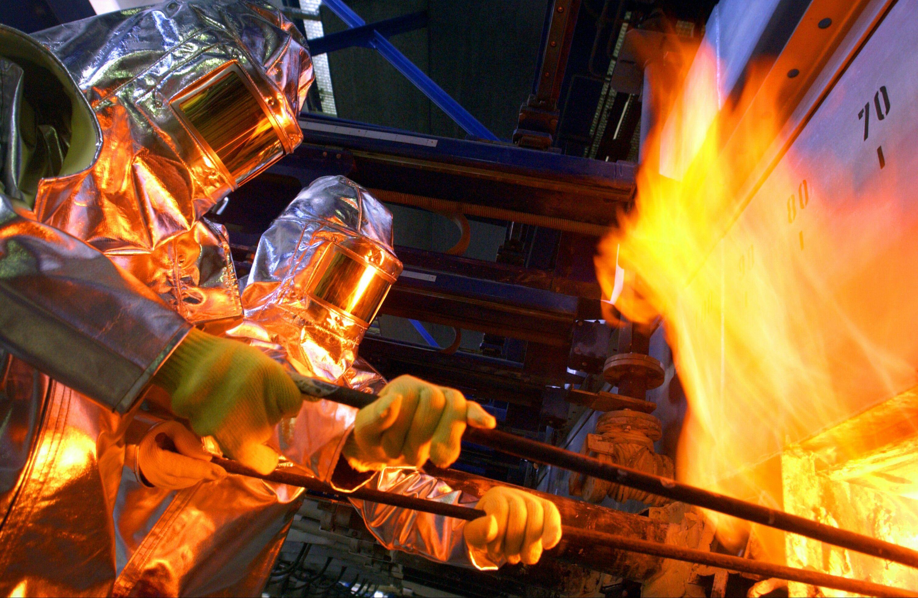 Arbeiter in Hitzeschutzkleidung an einer Glasschmelzwanne.