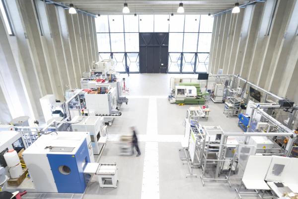 Halle der Forschungsfabrik ETA-Fabrik von oben mit mehreren Maschinen einer metallverarbeitenden Produktion.
