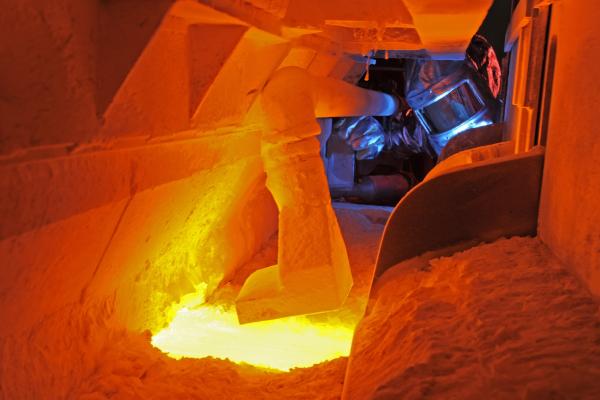 Ein Mann in Hitzeschutzkleidung kontrolliert die ordnungsgemäße Einlage des Rohstoffgemenges in die Schmelzwanne.
